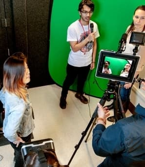 Students and a professor using a multimedia studio